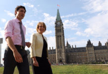 Prime Minister Justin Trudeau walks with Chief Science Advisor Mona Nemer in front of Canada's parliament